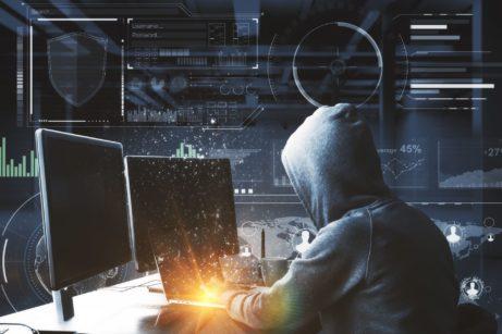 Hacker sedící započítačem se snaží nabourat dopodnikové sítě